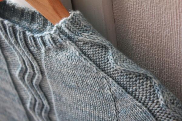 Gros plan sur l'encolure et les manches marteau torsadées du pull pour enfants Frozen, patron de tricot de Julie Partie