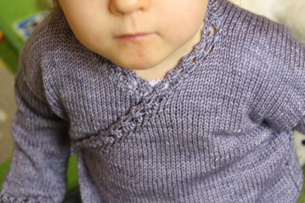 Display of the Fleur de Badiane baby wrap cardigan, a knitting pattern designed by Julie Partie