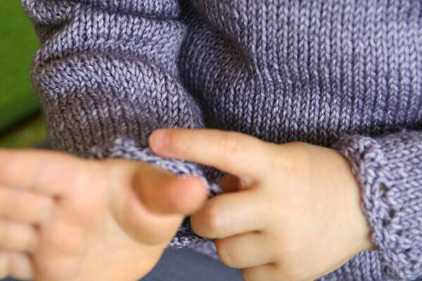 Detail of the Fleur de Badiane baby wrap cardigan, a knitting pattern designed by Julie Partie