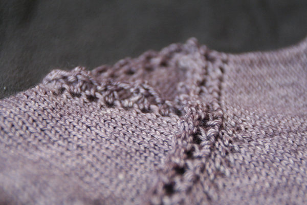 Zoom on the lace border of the Fleur de Badiane baby wrap cardigan, a knitting pattern designed by Julie Partie