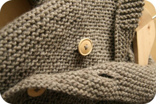 Zoom on the buttoning of the baby coat Le Manteau de Lino, a free knitting recipe for a baby coat in garter stitch in size 9 / 12 months