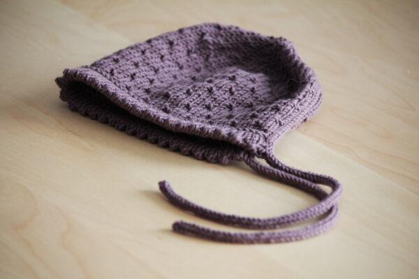 Présentation du Béguin de Printemps de Julie Partie, patron de tricot pour un petit bonnet de bébé au point de semis à ourlet en dent de chat