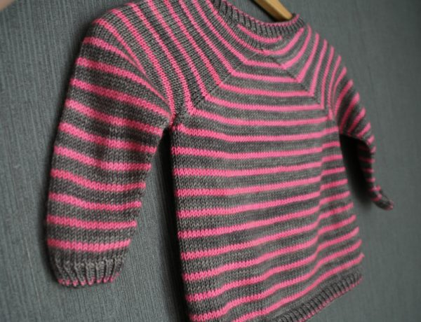 Display of the Cool Summer sweater, a knitting pattern designed by Julie Partie for a child's striped sweater with original raglan sleeves