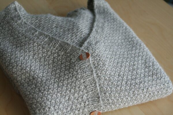 Display of the Comfort Zone cardigan, knitting pattern designed by Julie Partie for a garter slip stitch cardigan with deep V-neck and pockets