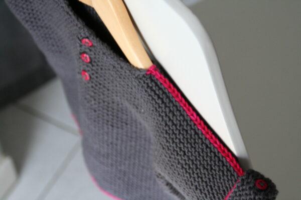 Gros plan sur le détail de boutonnage et de ligne colorée du pull pour enfant N e o n de Julie Partie, patron de tricot