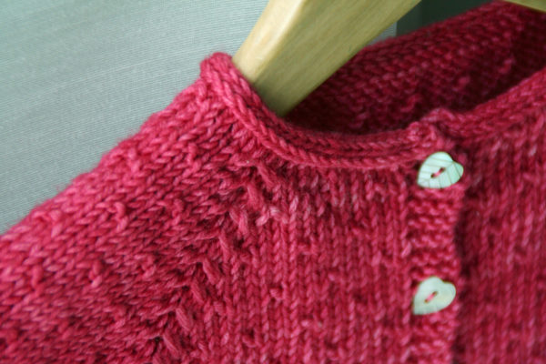 Zoom on the detail of the raglan sleeves of the Semis de Printemps cardigan, a knitting pattern designed by Julie Partie to create a cute cardi for little girls