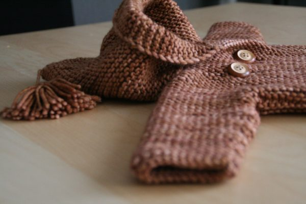 Display of the Jules baby coat, knitting pattern by Julie Partie