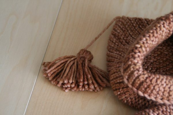 Zoom on the hood tassel of the Jules baby coat, a knitting pattern by Julie Partie