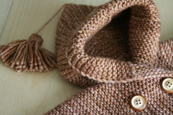 Zoom on the hood of Jules baby coat, a knitting pattern by Julie Partie