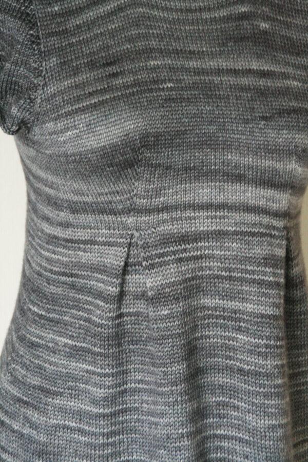 Gros plan sur les plis creux mettant en forme la jupe de la tunique pour femme Lisette de Julie Partie, patron de tricot pour un haut de forme peplum avec empiècement ajusté