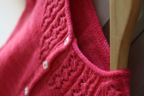 Gros plan sur les finitions d'encolure du gilet pour fille Little Trellis de Julie Partie, patron de tricot pour un cardigan intemporel boutonné à empiècement dentelle