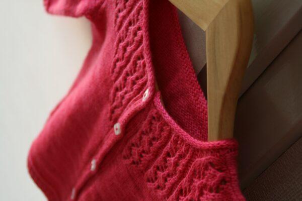 Gros plan sur l'empiècement dentelle du gilet pour fille Little Trellis de Julie Partie, patron de tricot pour un cardigan intemporel boutonné