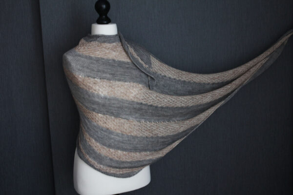Display of the Soften shawl, knitting pattern designed by Julie Partie for a two-colour shawl using fading yarn colours and alternating stockinette stitch and lace