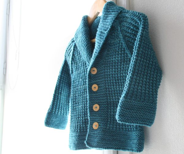 Display of the Oscar cardigan, a knitting pattern designed by Julie Partie for a cute grandpa cardi for baby and children with a vintage feel