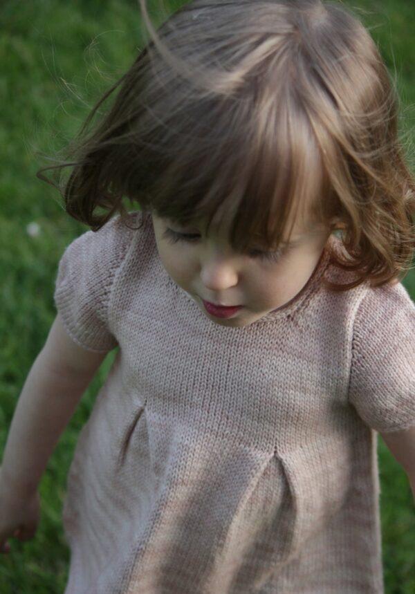 Présentation du haut Petite Lisette, patron de tricot de Julie Partie pour un top pour petite fille à manches courtes ballon et basque à pinces