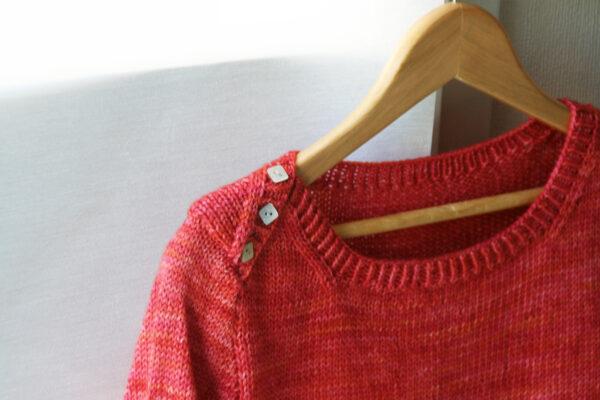 Gros plan sur le détail d'encolure boutonné du pull pour enfant Petit Large, patron de tricot de Julie Partie