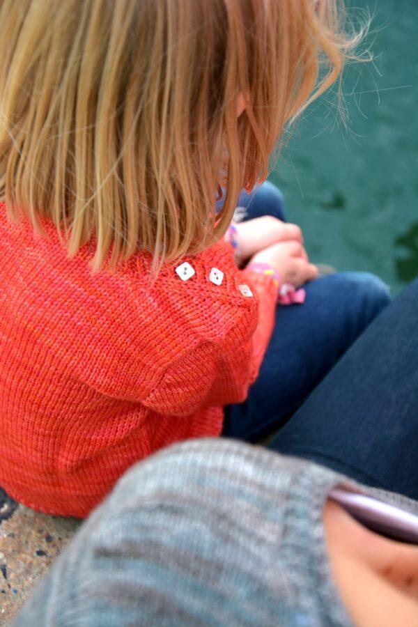 Gros plan sur le détail d'encolure boutonné du pull pour enfant Petit Large de Julie Partie