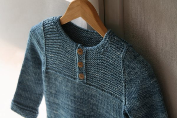 Zoom on the garter stitch yoke and buttoned collar of the children sweater Thistle, a knitting pattern designed by Julie Partie