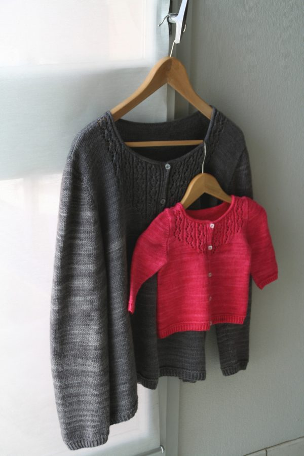 Display of two Trellis cardigans, one for women and one for children, knitting pattern designed by Julie Partie