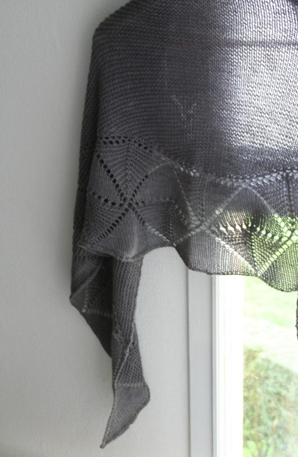 Display of the Swinging Triangles shawl designed by Julie Partie, a knitting pattern for a garter stitch shawl with a pretty lace edging