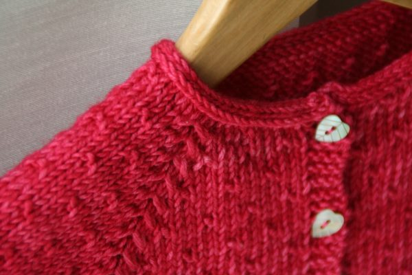 Zoom on the detail of the i-cord collar of the Semis de Printemps cardigan, a knitting pattern designed by Julie Partie to create a cute cardi for little girls