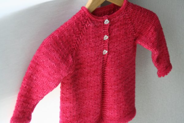 Display of the cardigan for little girl Semis de Printemps, knitting pattern by Julie Partie