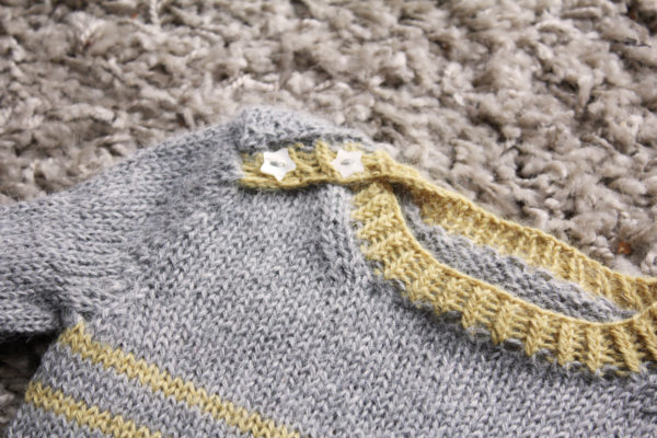 Zoom on the finishes of the baby sweater Tout Petit Large, a knitting pattern by Julie Partie