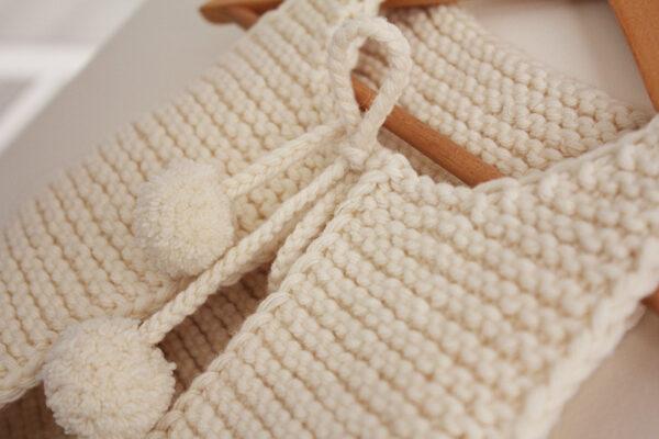 Gros plan sur le lien de fermeture du gilet de berger Lil Shepherd, patron de tricot créé par Julie Partie
