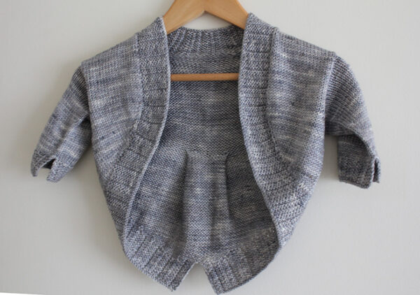 Display of the Petite Fille Modèle shrug, a knitting pattern designed by Julie Partie