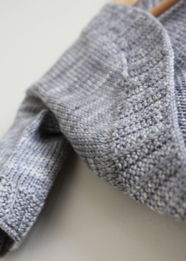 Zoom on the pleated rib border of the Petite Fille Modèle shrug, a knitting pattern designed by Julie Partie