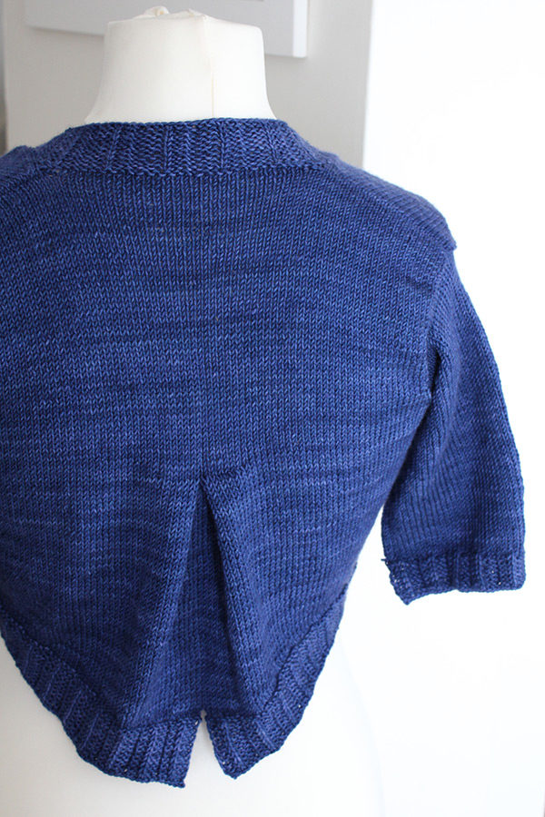 Zoom on the box pleat detail on the back of the Grande Fille Modèle shrug, a knitting pattern designed by Julie Partie