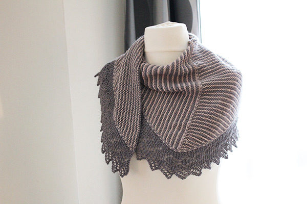 Display of the Setina shawl, a knitting pattern designed by Julie Partie, combining an original construction featuring stripes and a lace border