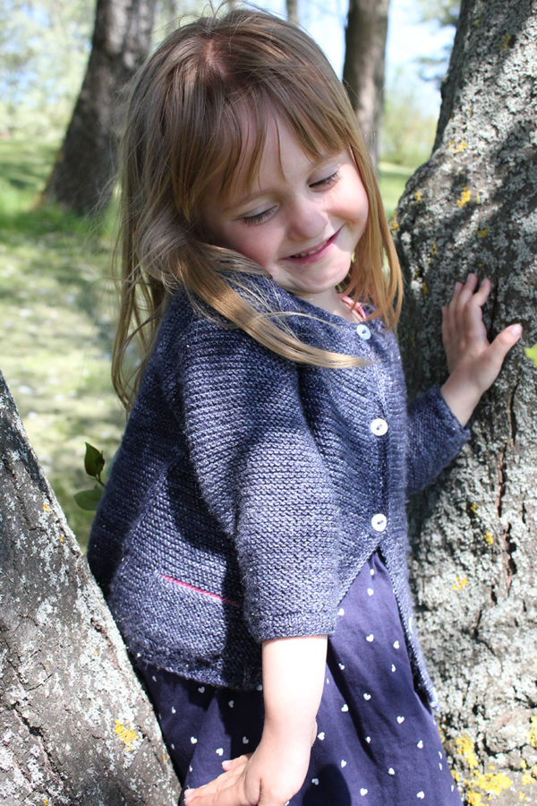 Display of the Starlette cardigan, a knitting pattern designed by Julie Partie for her little girl, knitted in garter stitch with contrasting secret pockets