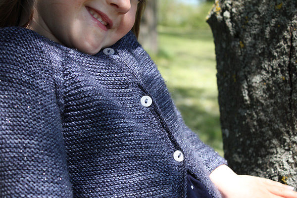 Zoom on the buttoning detail of the Starlette cardigan, a knitting pattern designed by Julie Partie