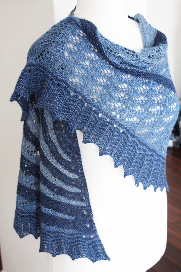 Display of the Dilué shawl, knitting pattern designed by Julie Partie using 2 skeins of gradient fingering yarn and alternating lace and garter stitch