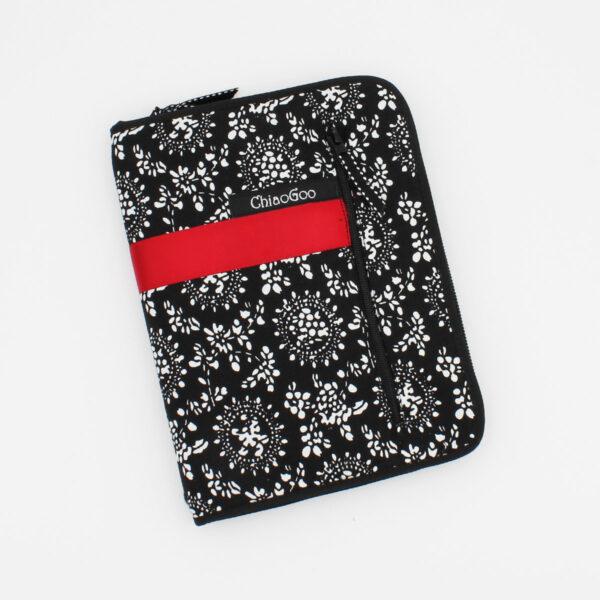 Pochette du kit d'interchangeables ChiaoGoo Twist, en tissu fleuri noir et blanc à bandes rouges, fermée, sur fond blanc