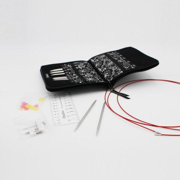Présentation du kit complet d'aiguilles circulaires interchangeables ChiaoGoo Twist en métal. Les pointes sont rangées dans la pochette en tissu ouverte, une paire de pointes est présentée à part accompagnée d'une jauge à aiguilles, de câbles et d'accessoires