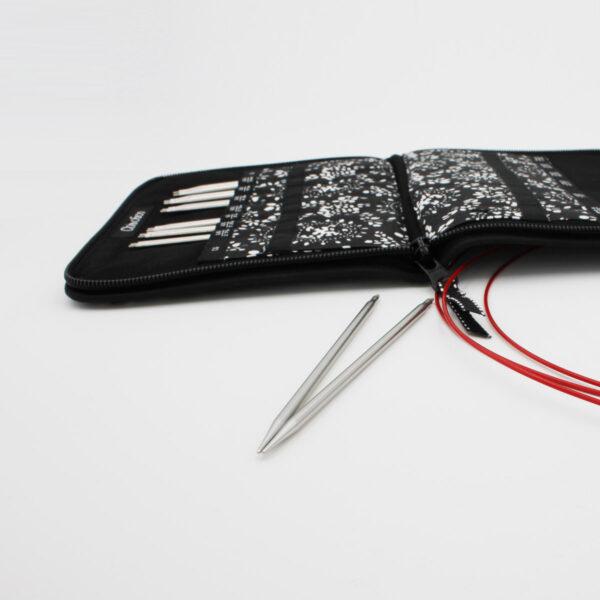 Kit d'aiguilles interchangeables ChiaoGoo TWIST, les pointes sont rangées dans les compartiments numérotés à l'intérieur de la pochette en tissu noir et blanc de la marque, deux pointes sont posées à côté de la pochette avec des câbles en nylon rouge TWIST