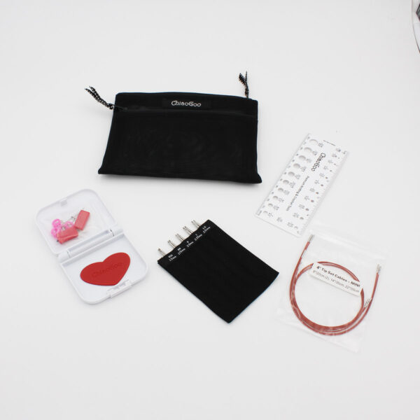 ChiaoGoo Twist Mini Set, the needle tips are presented in their organizer, next to the red cables, the nylon pouch and the open notions box, complete with heart grip, markers, gauge and accessories