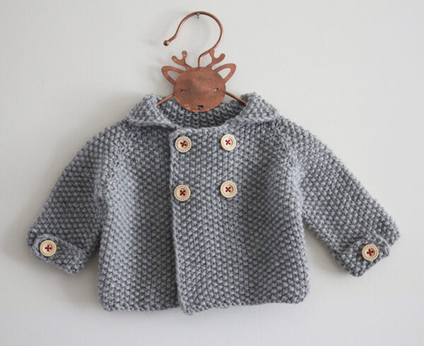 Display of the baby cardigan Camille, designed by Julie Partie, featuring beautiful finishes such as crossed lapels and button tabs on the sleeves, and knitted in seed stitch