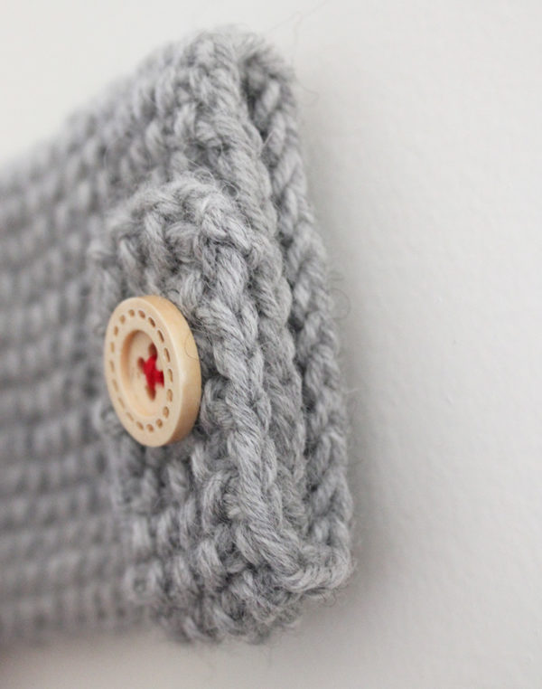 Zoom on the button tabs on the sleeves of the baby cardigan Camille, designed by Julie Partie, featuring beautiful finishes such as crossed lapels, and knitted in seed stitch