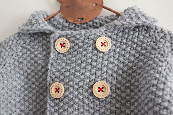 Zoom on the crossed lapels of the baby cardigan Camille, designed by Julie Partie, featuring beautiful finishes such as a cute collar and button tabs on the sleeves, and knitted in seed stitch