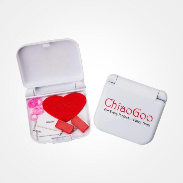 Présentation du kit d'accessoires ChiaoGoo Mini Twist, boîte en plastique blanc avec le logo de la marque, ouverte, contenant un grip en forme de coeur rouge, des stoppeurs de câbles rouges, des marqueurs roses et des clés de serrage