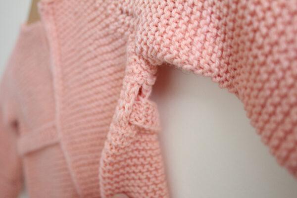 Gros plan sur le détail de la ceinture de la brassière pour bébé Madeline, patron de tricot créé par Julie Partie