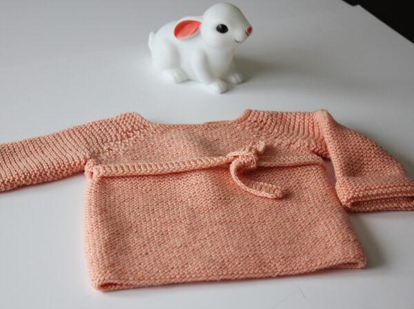 Présentation de la brassière Madeline, patron de tricot pour bébé créé par Julie Partie, au point mousse, avec un détail de dentelle et une fine ceinture