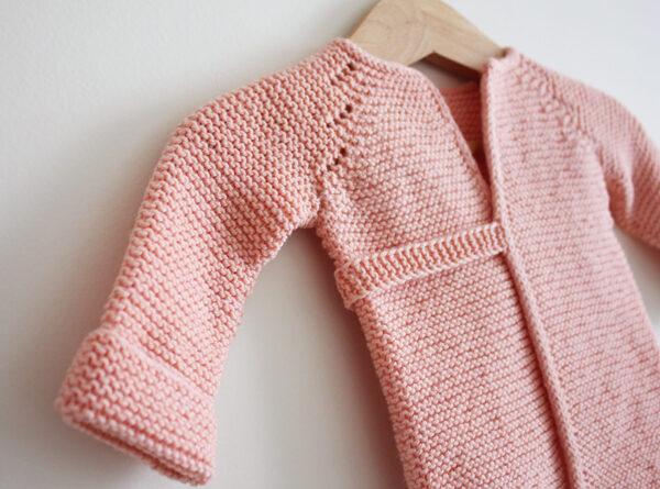 Présentation du dos de la brassière Madeline, patron de tricot pour bébé créé par Julie Partie, au point mousse, avec un détail de dentelle et une fine ceinture