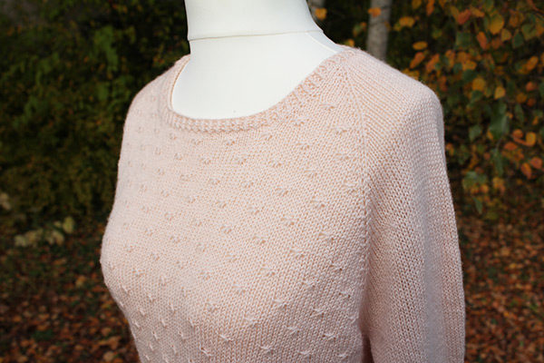 Gros plan sur le devant et l'encolure du pull Mollie de Julie Partie tricoté en Semilla de BC Garn coloris Nude