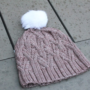 Display of the Nival hat as knitted following Julie Partie's design, featuring cables and a pompom