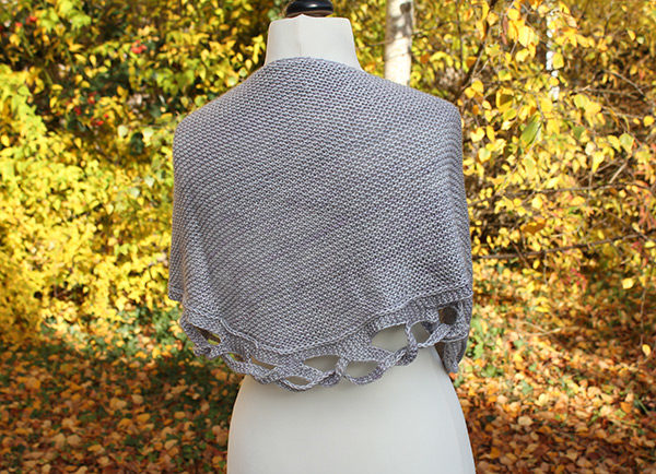 Display of the Tiara shawl designed by Julie Partie, knitting pattern to create a semi-circular shawl in garter stitch with an original braided edging