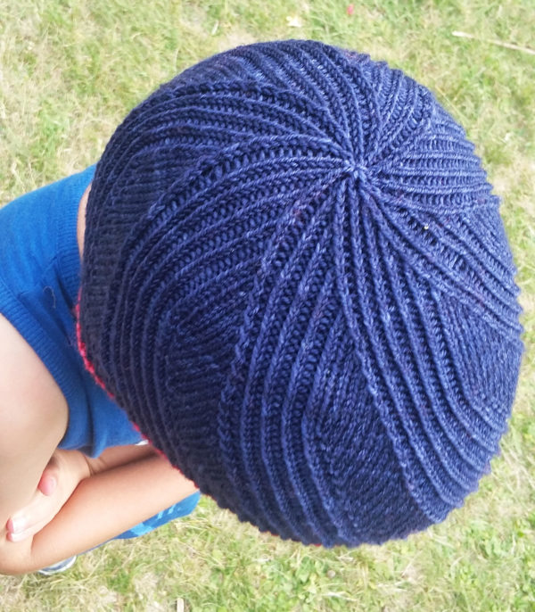 Display of the crown of the twisted stitches side of the reversible Winter in August hat, a knitting pattern designed by Julie Partie